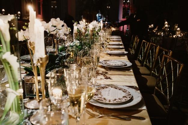 De feestelijke tafel in het restaurant is versierd met kaarsen en bloemen