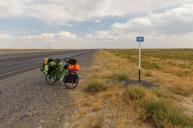 De fiets voor een reiziger bevindt zich op de weg dichtbij een kilometerteken, kazachstan