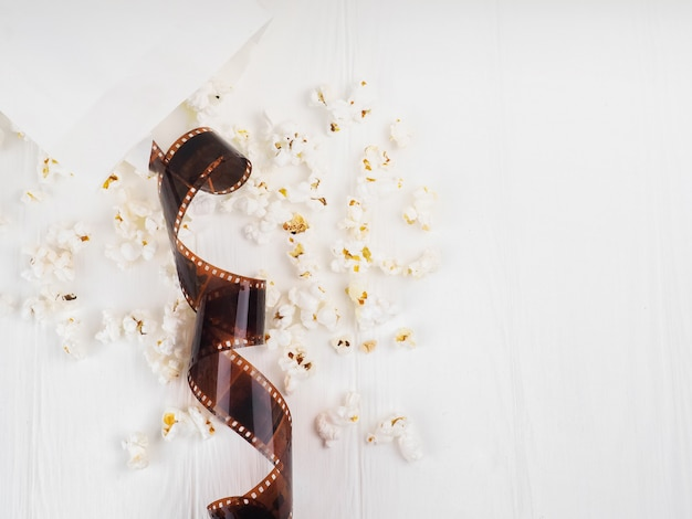 De film in de spiraal, nabij de popcorn, clapperboard kopie ruimte voor tekst.
