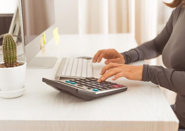De financieel manager leest het rapport op de rekenmachine.