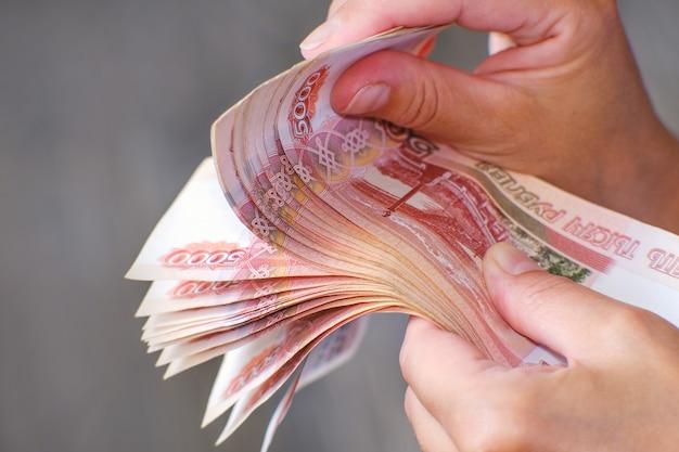 De financier heeft een bundel bankbiljetten in zijn hand. hij biedt leningen tegen rente en in termijnen
