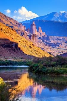 De fisher towers gedeeltelijk verlicht door de late middagzon weerspiegeld in de colorado-rivier in de buurt van moab, utah Premium Foto