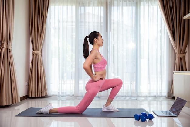 De fitnesstraining van de aziatische vrouw thuis. ze leert nieuwe oefeningen terwijl ze thuis online trainingshandleidingen over haar bekijkt.