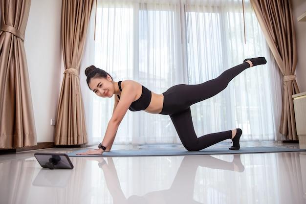 De fitnesstraining van de aziatische vrouw thuis.