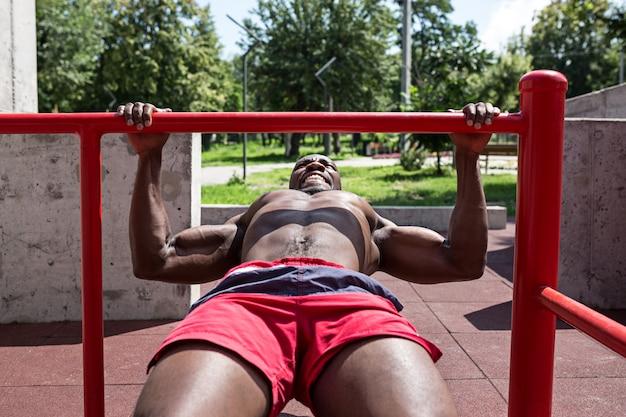 De fitte atleet die oefeningen doet. afro of afro-amerikaanse man buiten in de stad. trek sportoefeningen uit.