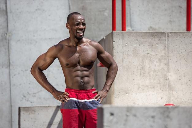 De fitte atleet doet oefeningen in het stadion. afro of afro-amerikaanse man buiten in de stad. trek sportoefeningen uit. fitness, gezondheid, lifestyle concept