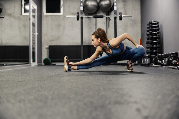 De fitte en slanke vrouw strekt de spieren van het hele lichaam uit door met het lichaam te stappen en te leunen en met één hand naar de voet toe