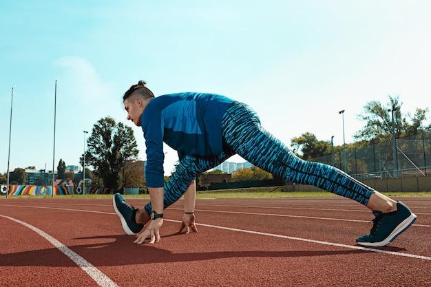 De fitte mannelijke loper die zijn benen uitrekt en zich voorbereidt op hardlopen tijdens de training op stadiontracks. de atleet, fitness, training, sport, oefening, training, atletisch, lifestyle concept