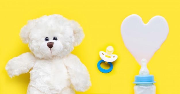 De fles melk voor baby en babyfopspeen met stuk speelgoed draagt op geel