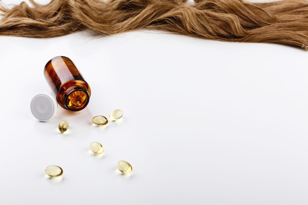 De fles met vitamines ligt vóór bruine haarkrul