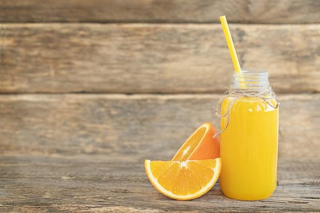 De fles sinaasappelsap en gesneden sinaasappel op de houten tafel