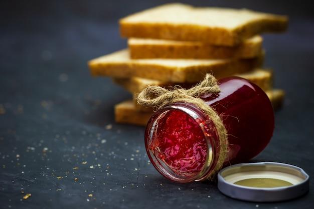 De fles van de aardbeijam en volkorenbrood worden gestapeld op een zwarte achtergrond. concept ontbijt en gezond voedsel.