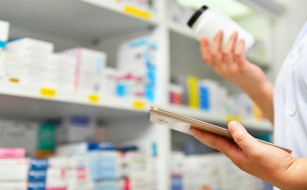 De fles van de apothekerholding geneeskunde en computertablet voor het vullen van voorschrift in apotheekdrogisterij.