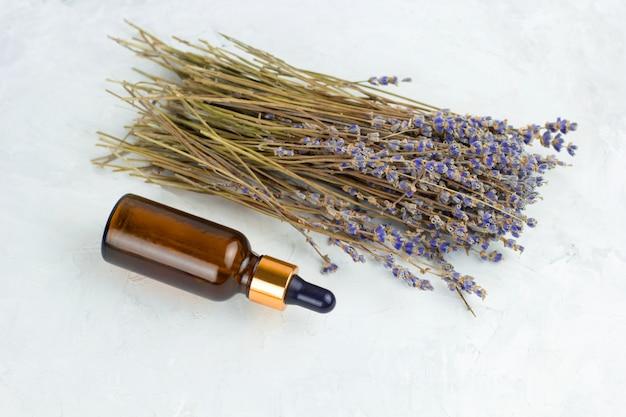 De fles van de lavendelolie met pipet en boeket van droge lavendel witte sjofele achtergrond