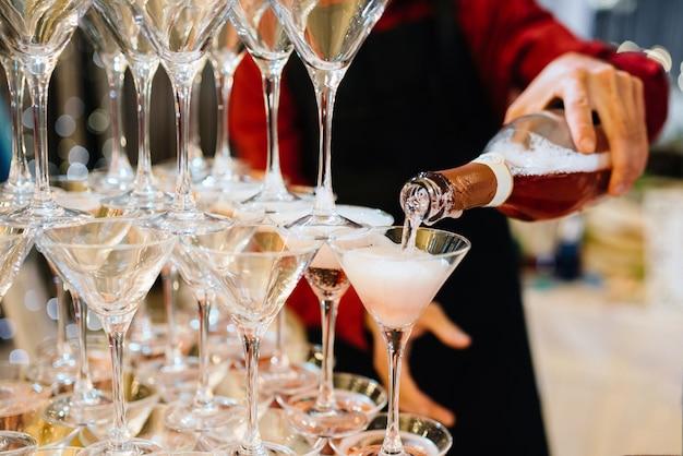 De fles van de persoonsholding champagne en dienende piramide van heerlijk drankje
