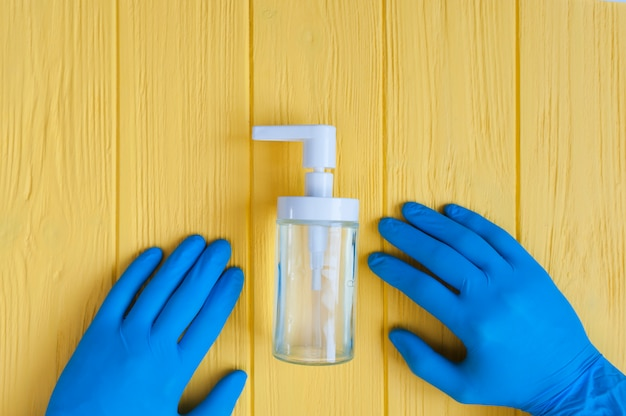 De fles van het handdesinfecterende middel en de blauwe gehandschoende handen sluiten omhoog. bel voor handdesinfectie. stop coronavirus concept
