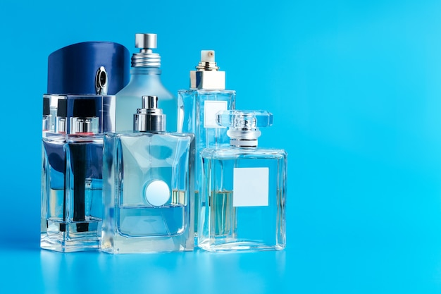 De fles van het mensenparfum op blauwe dichte omhooggaand