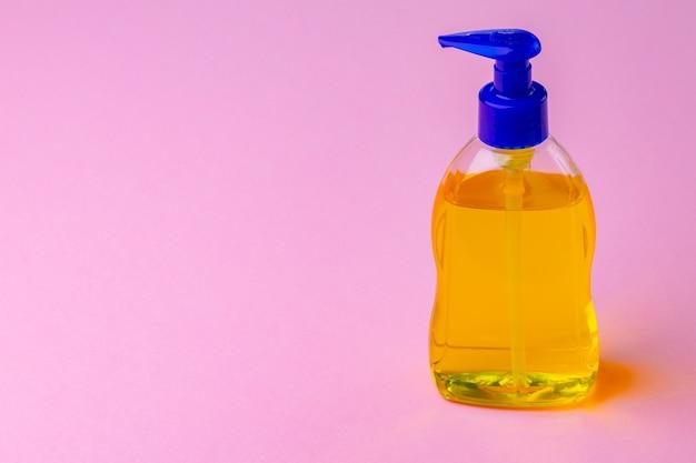 De fles vloeibare zeep en handdesinfecterend middel op roze achtergrond, sluit omhoog