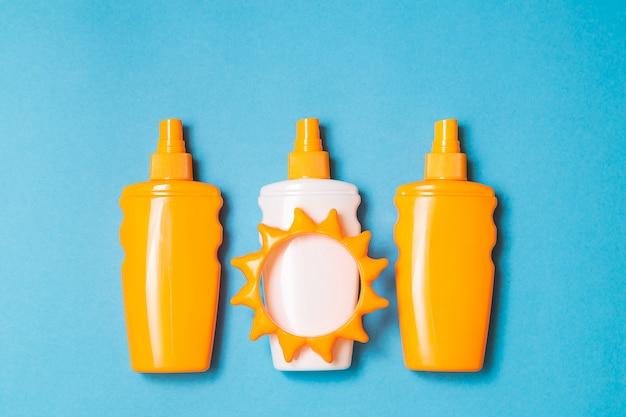 De fles zonneschermroom of lotion met zonstuk speelgoed vlakte lag op de blauwe achtergrond