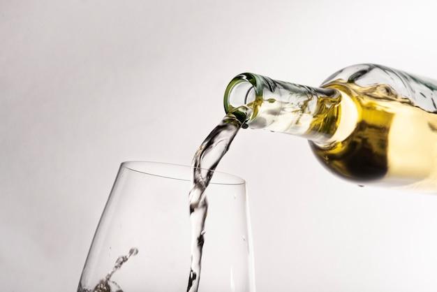 De flessen gietende wijn van de close-up in glas