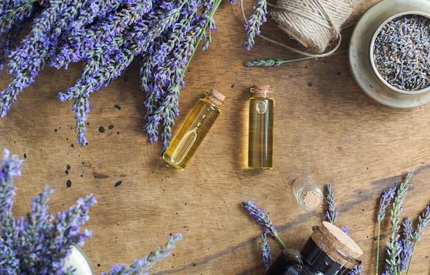 De flessen van de lavendelolie, natuurlijk kruid kosmetisch concept met flatlay lavendelbloemen