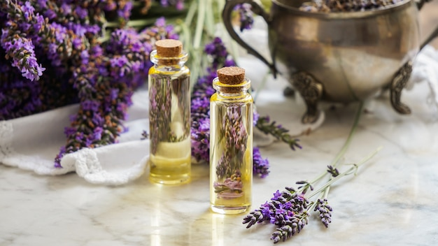 De flessen van de lavendelolie, natuurlijk kruidschoonheidsmiddel met lavendelbloemen op steenachtergrond