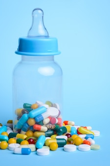 De flessenhoogtepunt van de baby` s melk van pillen en capsules tegen blauw