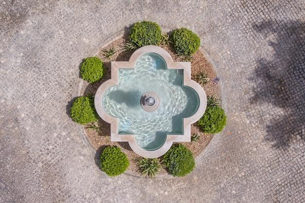 De fontein in de tuin van kasseien, van bovenaf vanuit de lucht geschoten, drone.