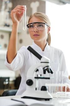 De formule is bijna compleet. mooie jonge vrouwelijke wetenschapper die een reageerbuis vasthoudt en ernaar kijkt terwijl hij in het laboratorium werkt