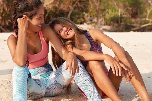 De foto's van gelukkige onbezorgde vrouwen zitten op warm zand