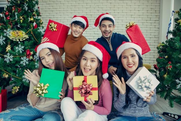 De foto toont een groep aziatische vrienden die kerstmis thuis vieren.