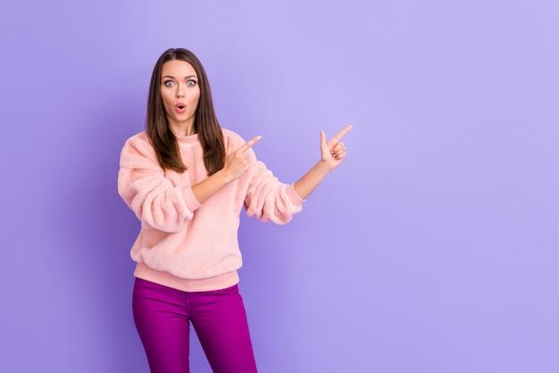 De foto van aantrekkelijke dame open mond geeft vinger lege ruimte op paarse achtergrond aan