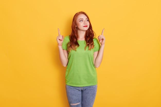 De foto van aantrekkelijke donkerharige jonge europese vrouw die met wijsvingers omhoog op exemplaarruimte richt, stelt tegen gele ruimte