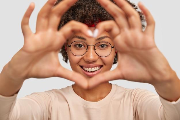 De foto van aantrekkelijke jonge vrouw maakt het gebaar van de hartvorm over gezicht
