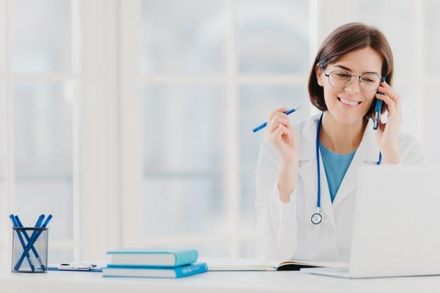 De foto van blije vrouwentherapeut of arts heeft telefoongesprek met patiënt