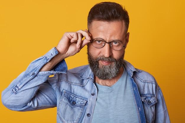 De foto van de bebaarde man op middelbare leeftijd houdt de hand op de rand van de bril en draagt casual kleding