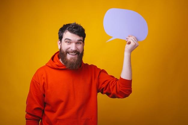 De foto van de gebaarde kerel houdt een lichtpaarse bellentoespraak op gele ruimte.