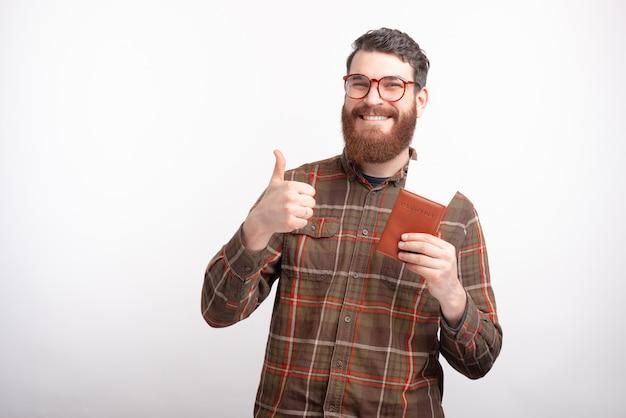 De foto van de glimlachende mens is klaar voor reis, houdend paspoort met kaartjes en het tonen van duimen