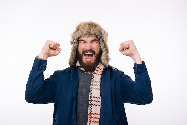 De foto van de verbaasde gebaarde mens die de winterkleren draagt, viert succes