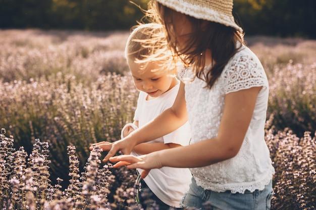 De foto van een blanke zus en een broer die in een lavendelveld lopen, werden in de zon gezonken en omringd door bloemen