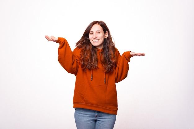 De foto van een jonge vrouw die bij de camera glimlacht en toont kent geen gebaar