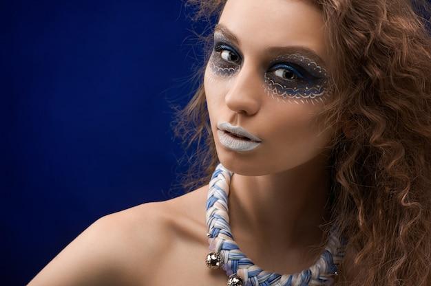 De foto van een mooi meisje met de originele make-up