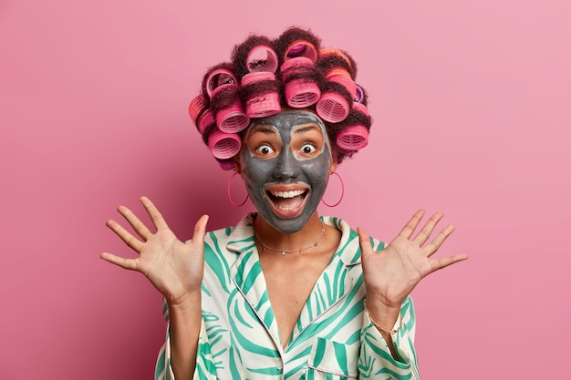 De foto van een positief jong vrouwelijk model werpt palmen op en bekijkt graag camera