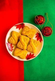 De foto van een stapel koekjes of zandkoekjes op het bord met rode belletjes. nationale koekjesdag achtergrond. kerstontbijt voor de kerstman.