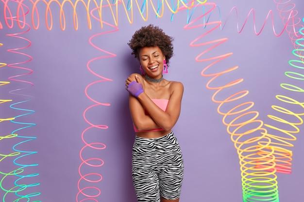 De foto van een tevreden donkere vrouw sluit de ogen, glimlacht breed, omhelst zichzelf, draagt sportkleding