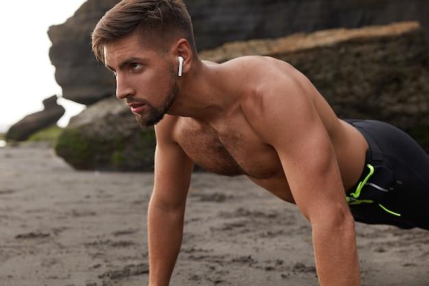 De foto van geconcentreerde sportman maakt de plank van de sportoefening