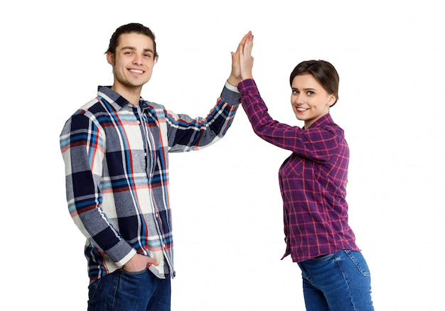 De foto van gelukkige jongerenman en vrouw in basiskleding geeft fife die over wit wordt geïsoleerd