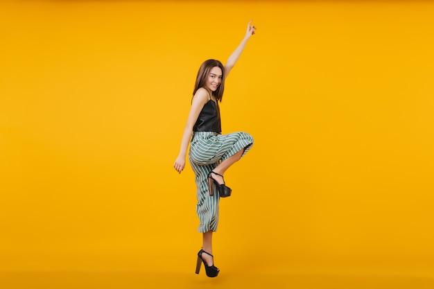 De foto van gemiddelde lengte van dansende donkerbruine vrouw draagt schoenen met hoge hakken. portret van mooi meisje springen.