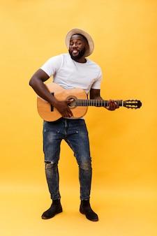 De foto van gemiddelde lengte van de opgewekte artistieke mens die zijn gitaar in toevallige reeks speelt. geïsoleerd op gele achtergrond.