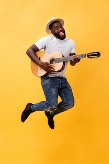 De foto van gemiddelde lengte van de opgewekte artistieke mens die zijn gitaar speelt. geïsoleerd op gele achtergrond.